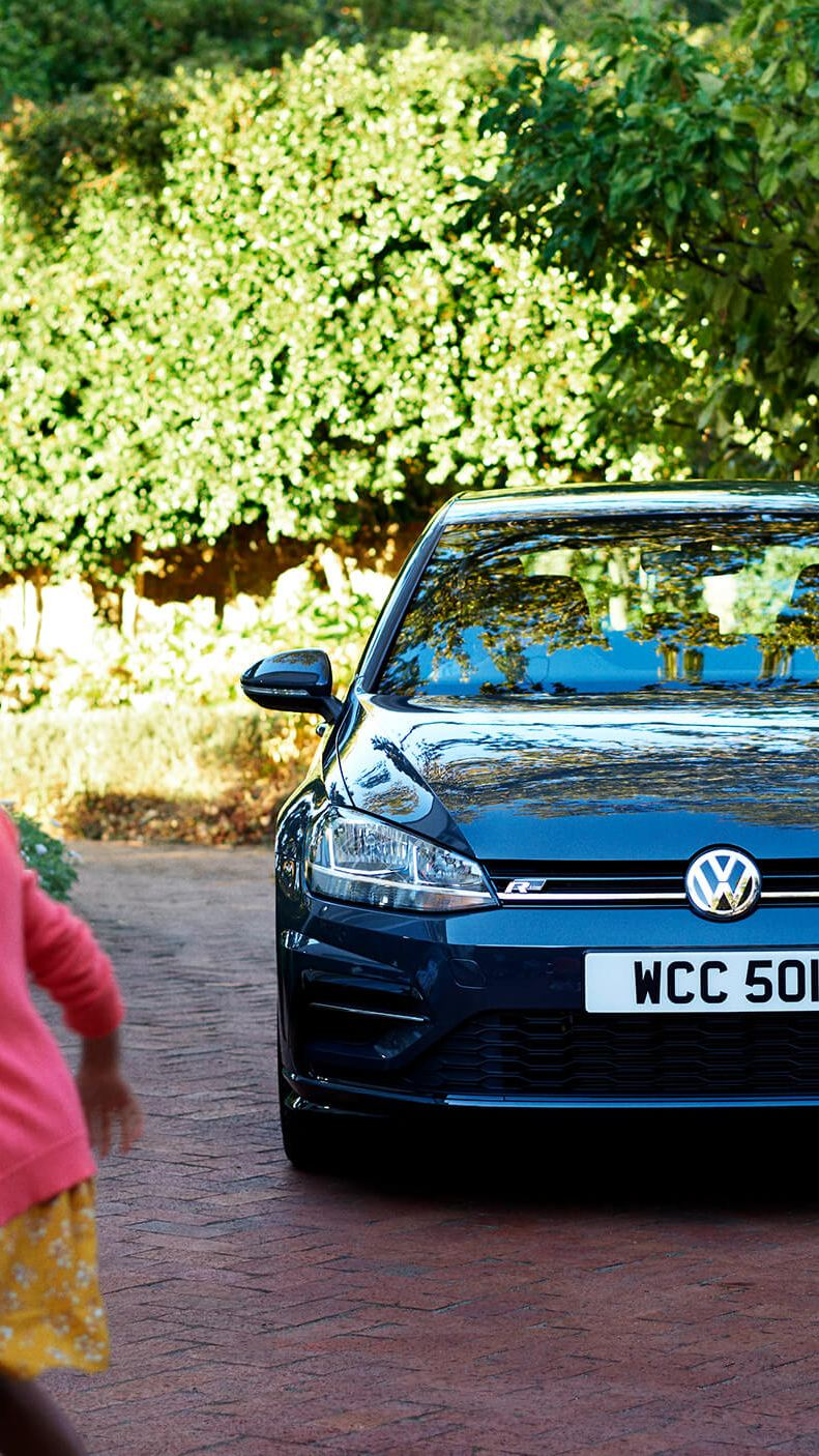 A black Volkswagen Golf next outside a family home, next a little girl with her pet dog.