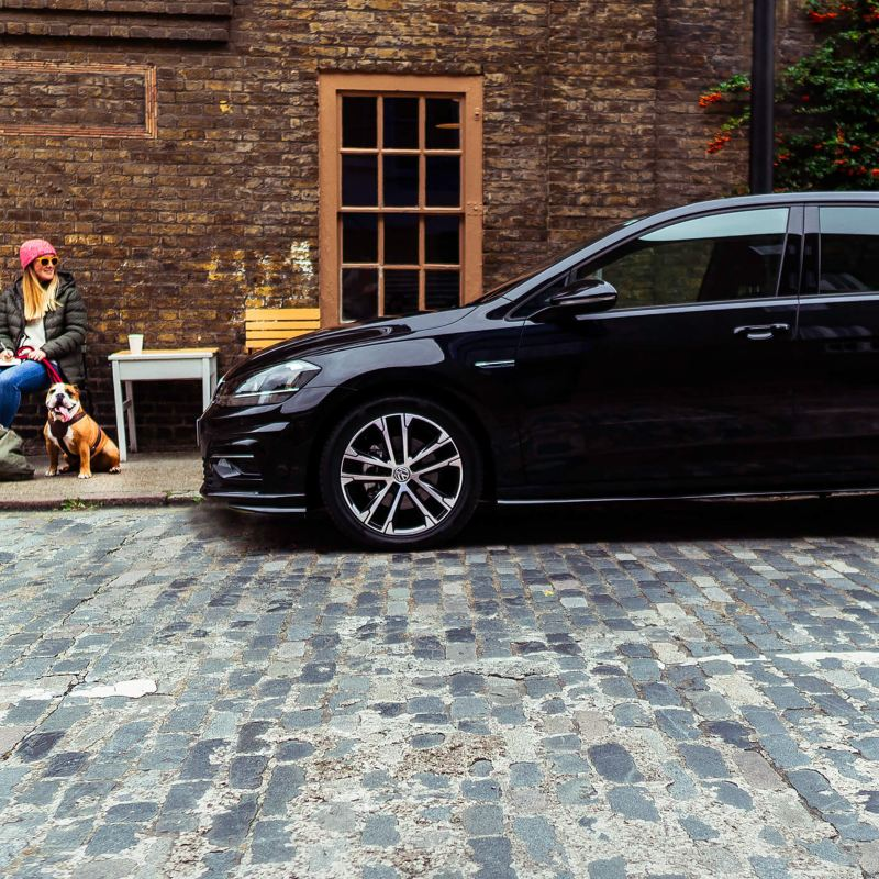 A lady sitting near a parked Volkswagen Golf