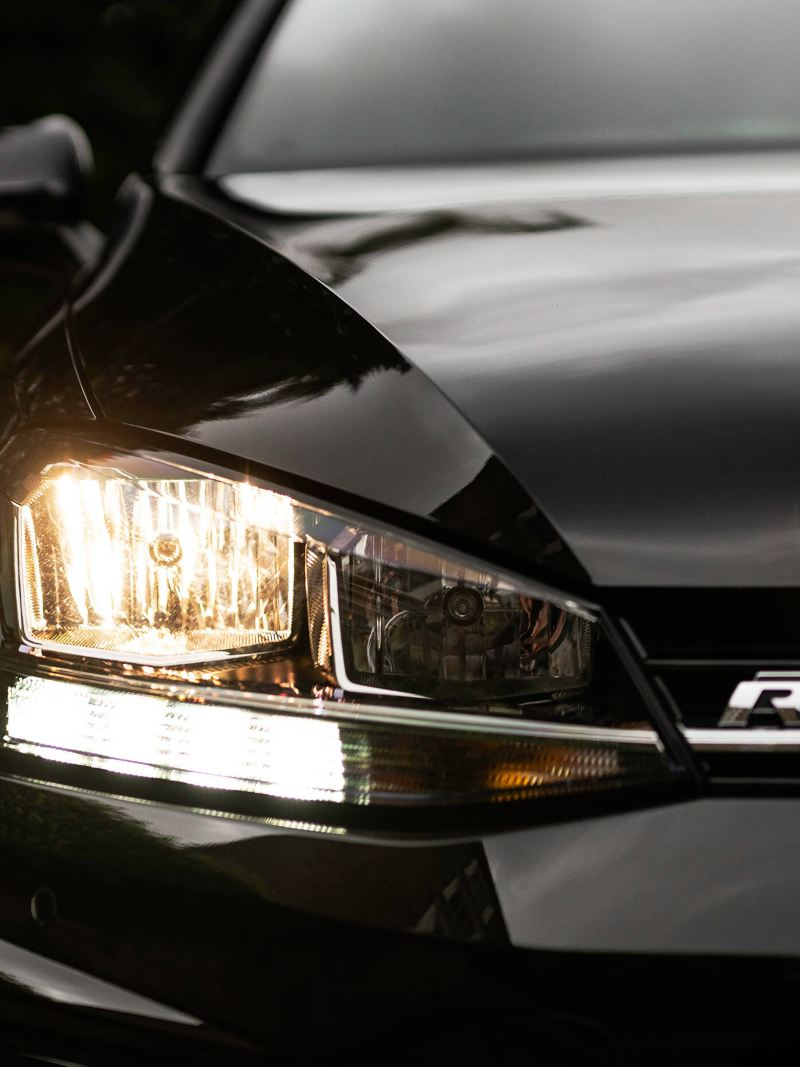 Black Volkswagen Golf R-Line with the front lights on