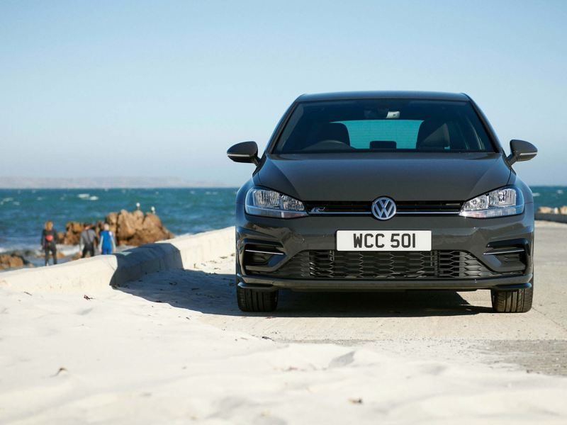 A grey Volkswagen Gold parked near the sea