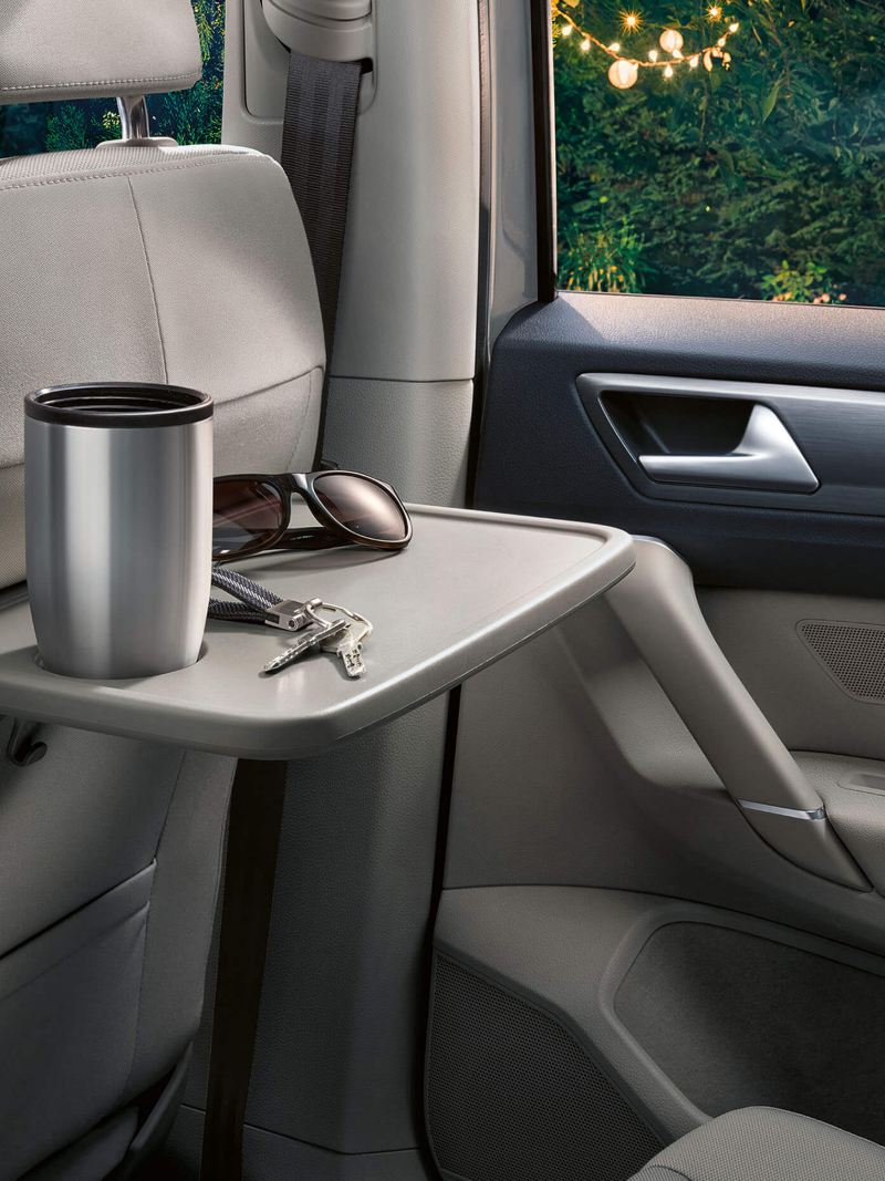 Interior shot of folding passenger tables in the Volkswagen Golf SV.