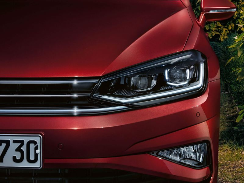 Front headlight shot of a red Volkswagen Golf SV.