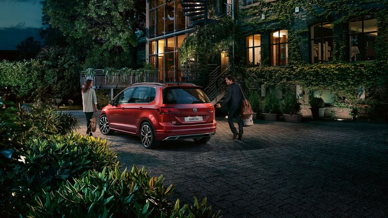 A couple entering a country hotel at night, walking away front their red Volkswagen Golf SV.