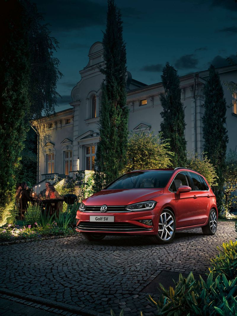 A red Volkswagen Golf SV, outside a country hotel at night.