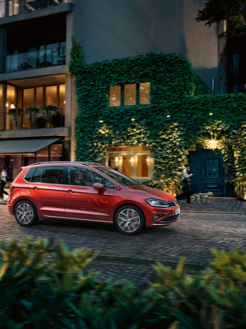 A red Volkswagen Golf SV driving on a lit cobbled street, bistros and a pedestrian walking their dog in the background.