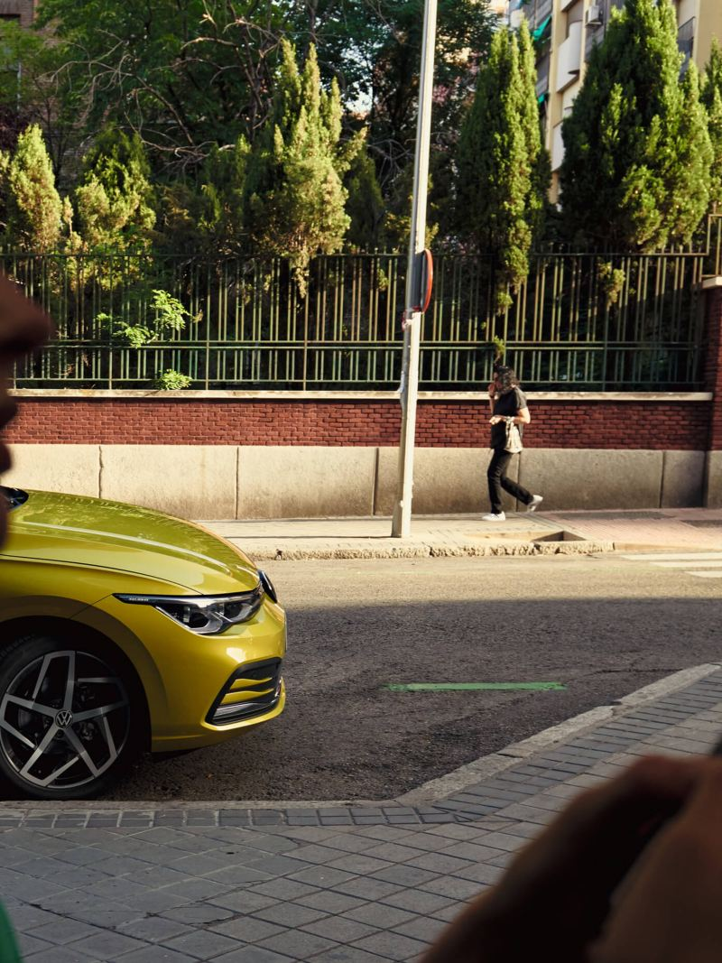 The woman using a phone while standing on the street in front of a yellow Golf 8