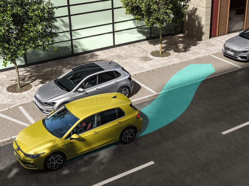 A yellow Volkswagen Golf 8 parking between two silver cars while using the Park Assist feature