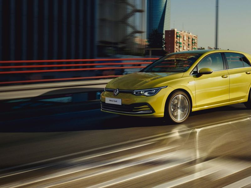 A yellow new Volkswagen Golf 8 driving on the road