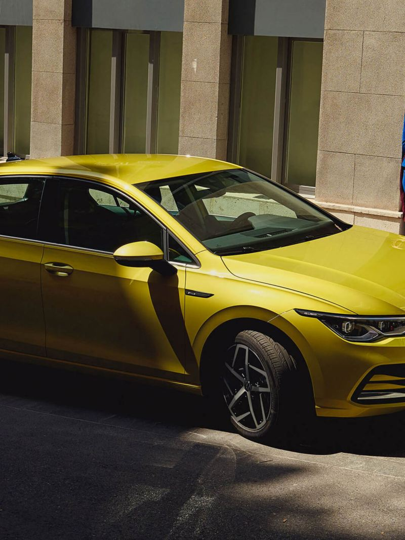 A woman waiting behind a yellow new Volkswagen Golf 8