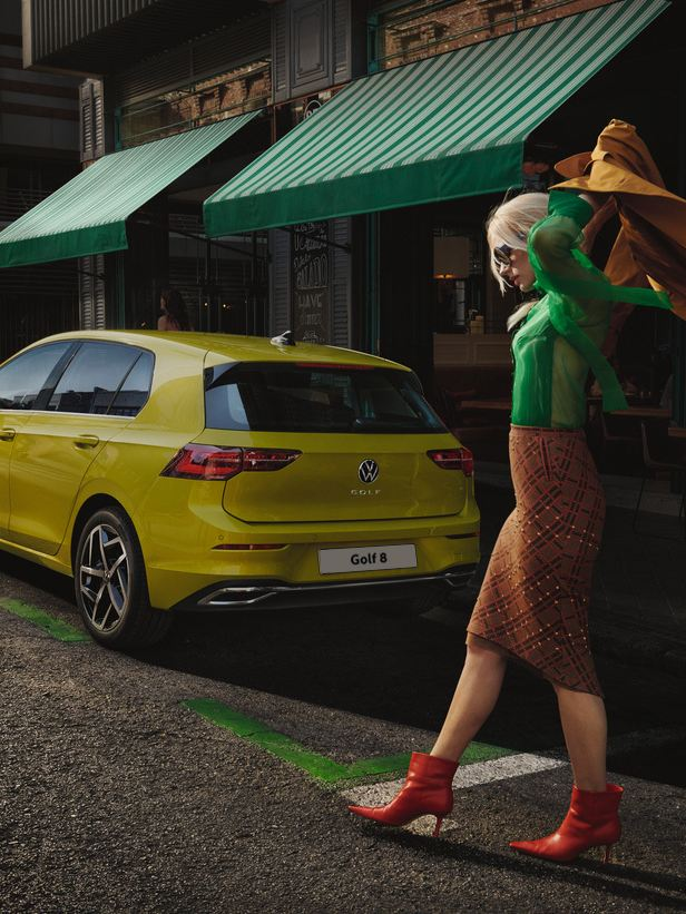 A couple taking photos in front of a yellow new Volkswagen Golf 8 in a fair