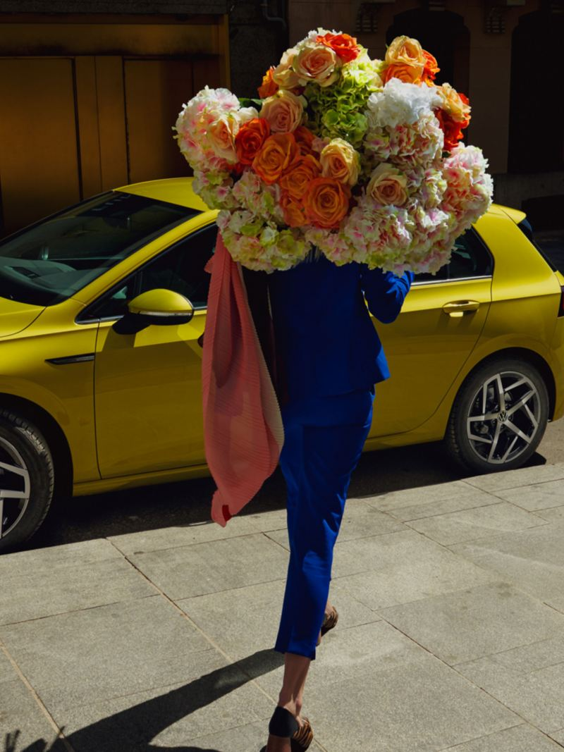 A woman with a huge bouquet of flowers walking away from her yellow Volkswagen Golf 8