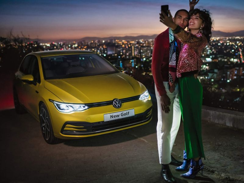 A couple stand in front of the Golf 8 overlooking a city