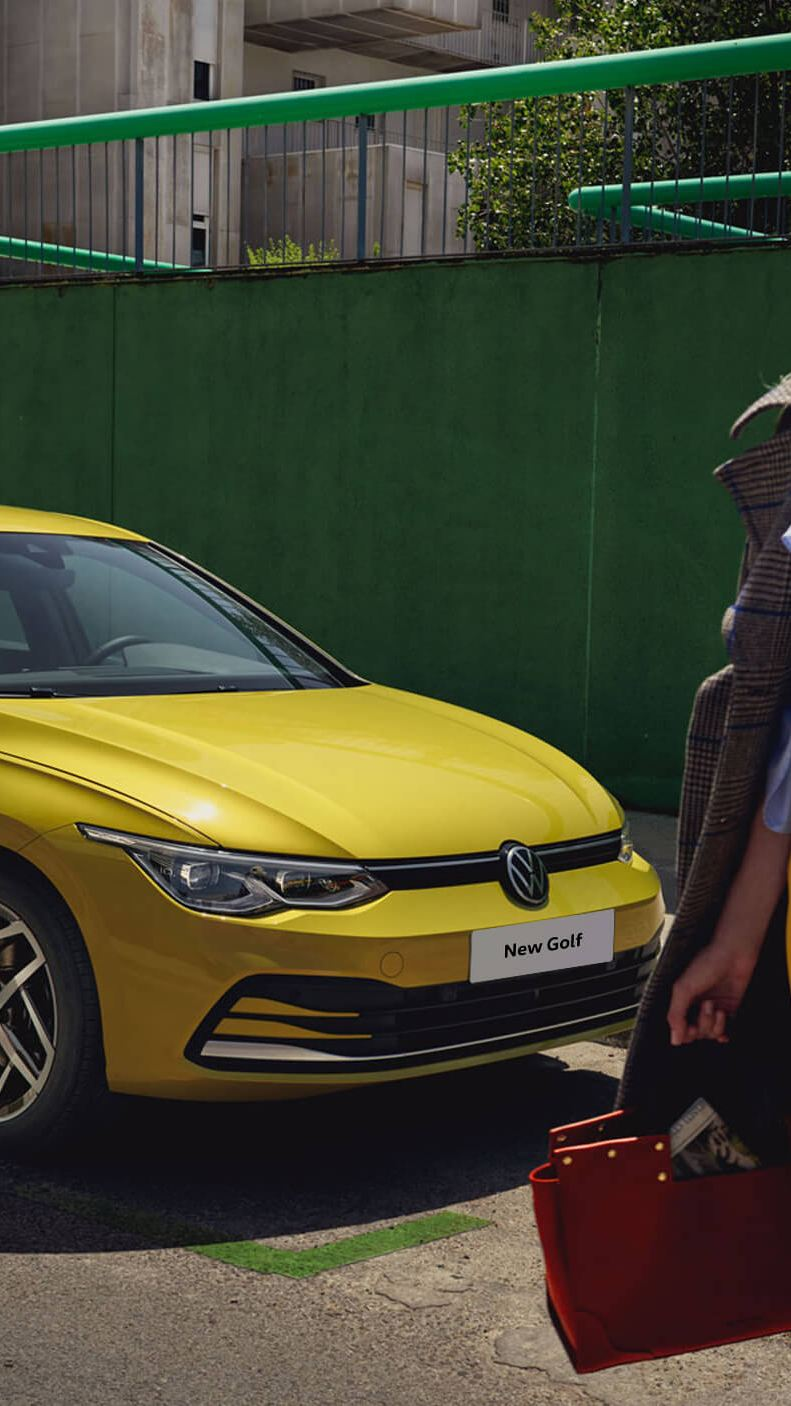 A woman in front of a yellow new Golf 8