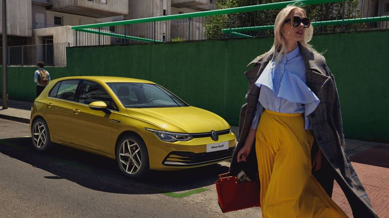 A yellow VW Golf 8 is parked on street with person walking in front of car with shopping
