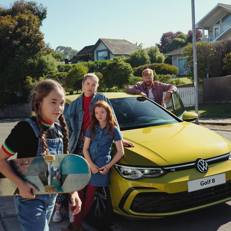 A family standing in front of their Golf 8