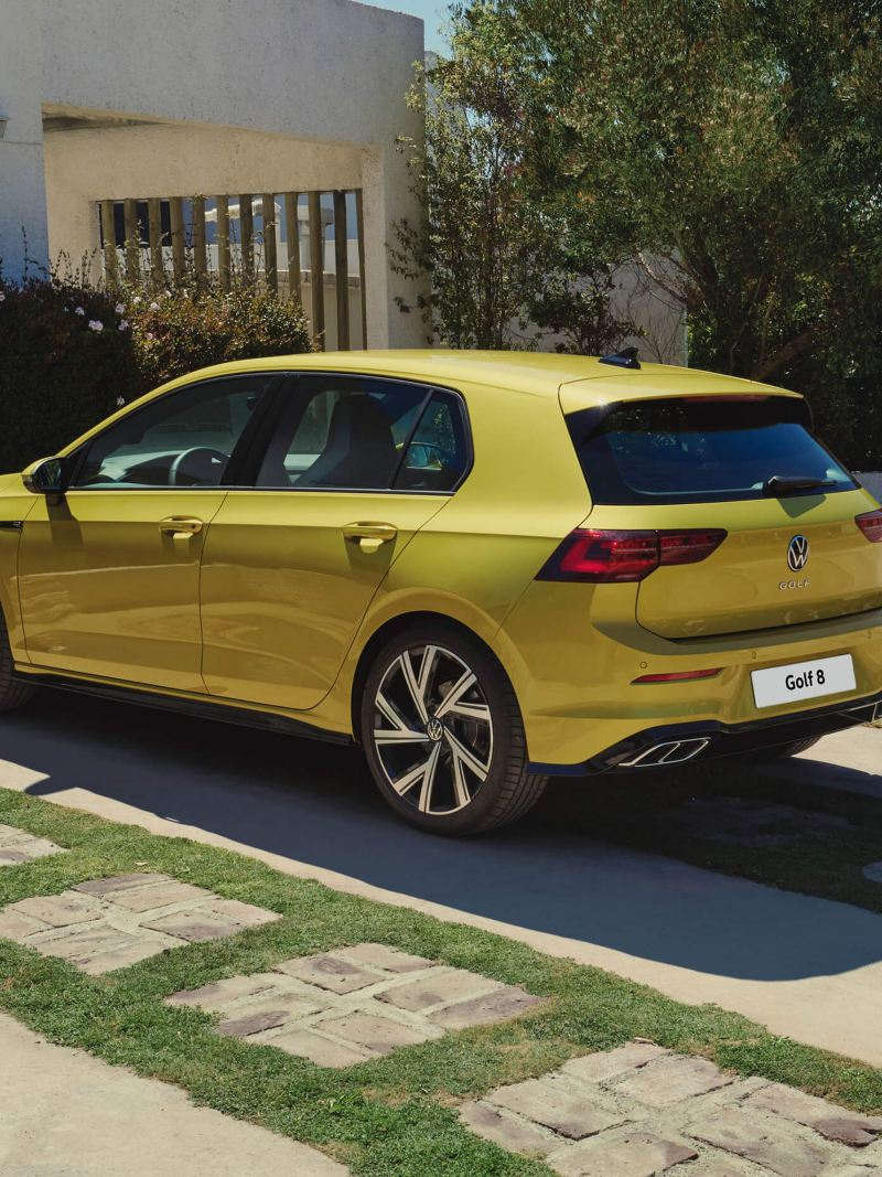 A yellow Volkswagen Golf 8 R-Line parked in front of a building