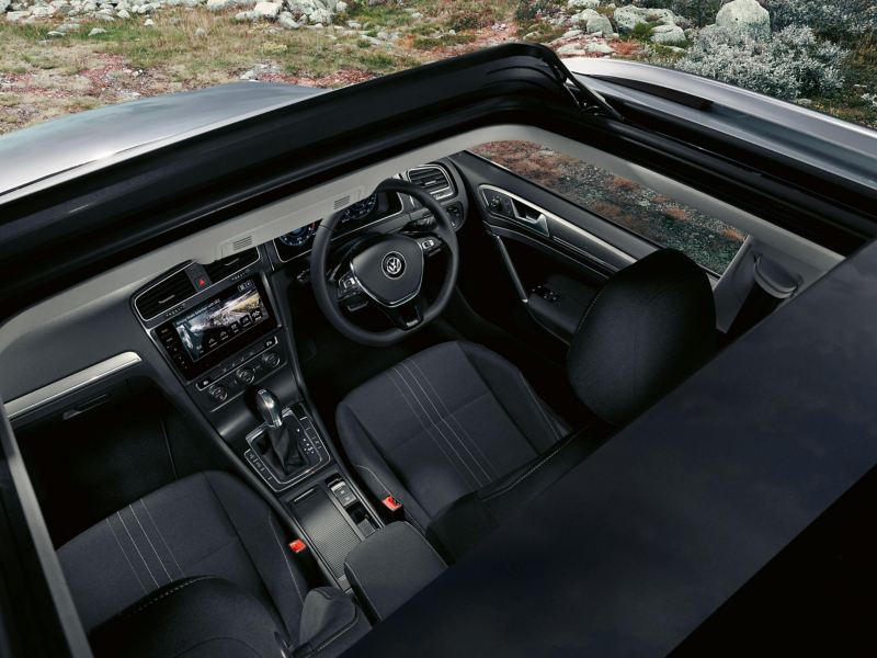 Interior shot of the Volkswagon Golf dash board and steering wheel, taken from above an open sunroof.