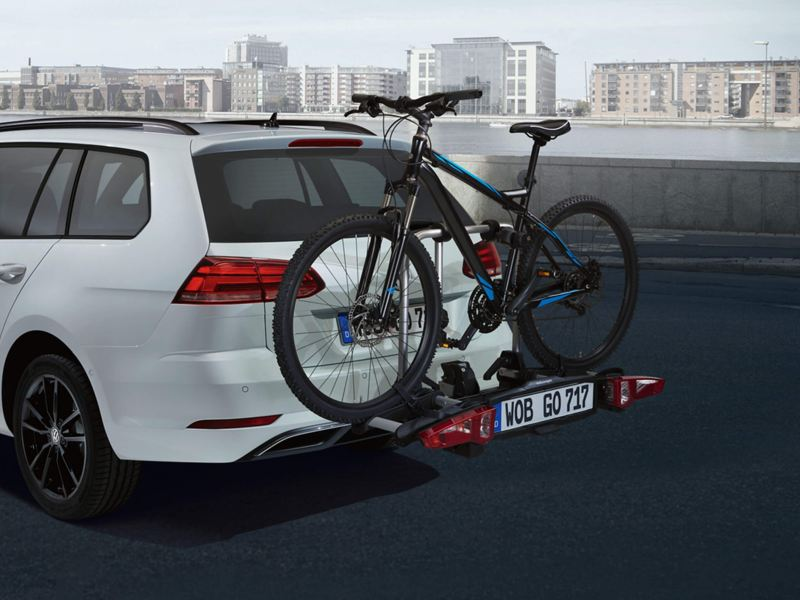 A white Volkswagen Golf Estate, with a bicycle on a rack.
