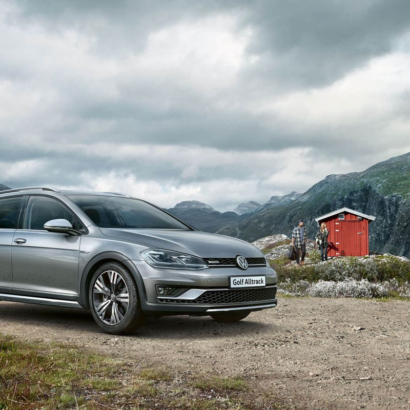 A silver Volkswagen Golf Estate, next to a cabin, in the mountains.