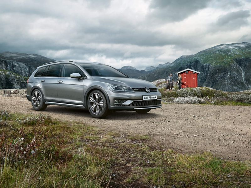 A grey Volkswagen Golf Estate, next to a cabin, in the mountains.