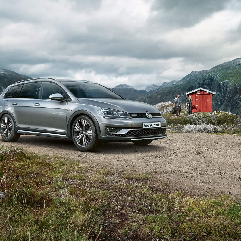 A silver Volkswagen Golf Alltrack Estate in a lay-by surrounded by mountains in the background