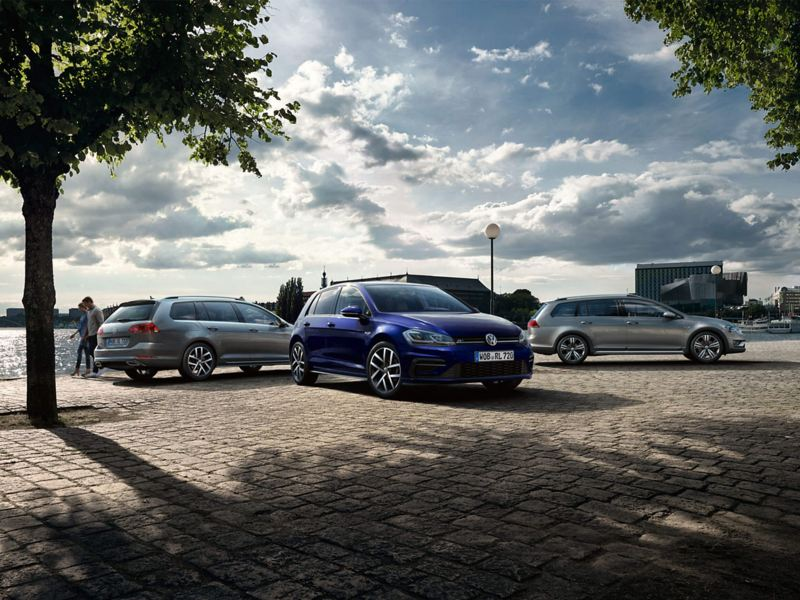 Three Volkswagen Golf Estates, all parked on a cobbled path next to a lake.