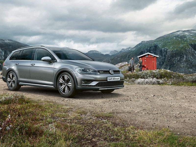 A silver Golf Alltrack, at a cabin in the mountains.