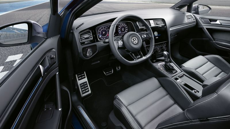 Interior shot of the Volkswagen Golf dash board and steering wheel, race track visible in the wing-mirror.
