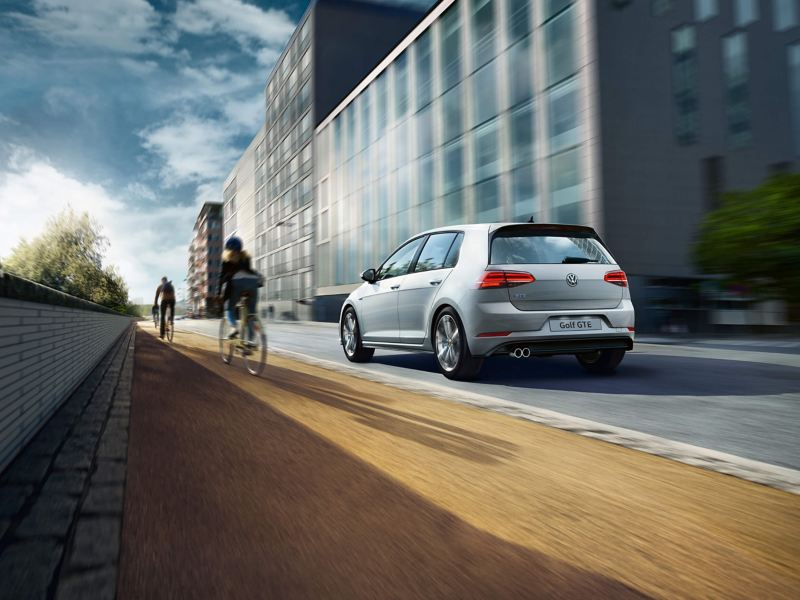 A white Golf GTE driving on the road along side cyclists.