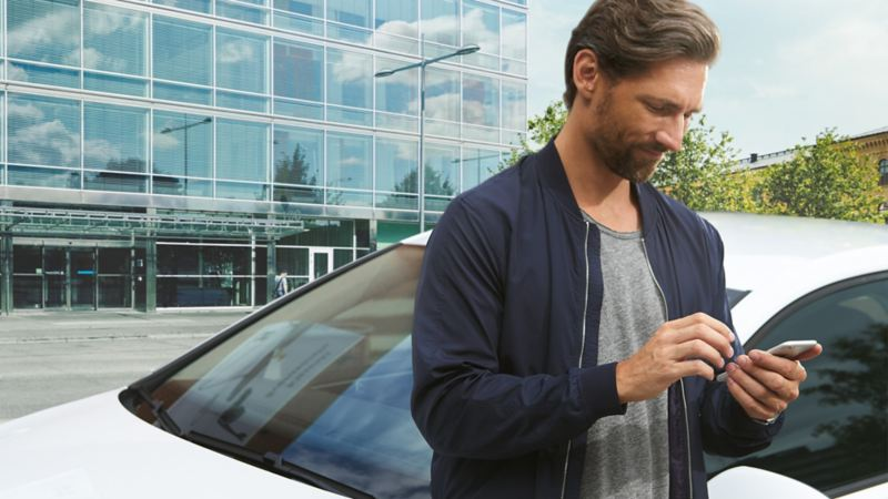 A man standing and using his phone infront of a white Golf GTE.
