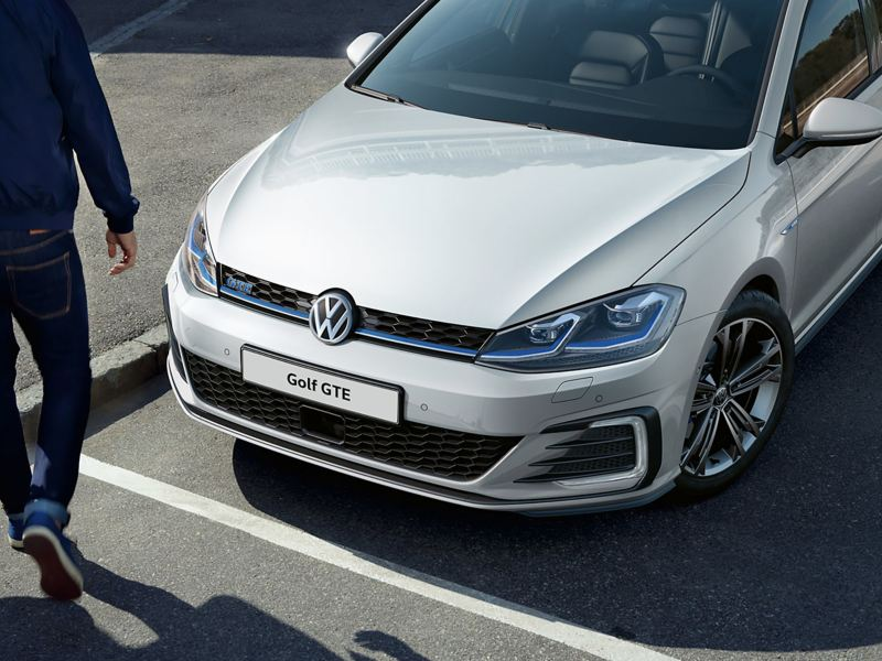 A parked white Golf GTE with a man walking infront of it.