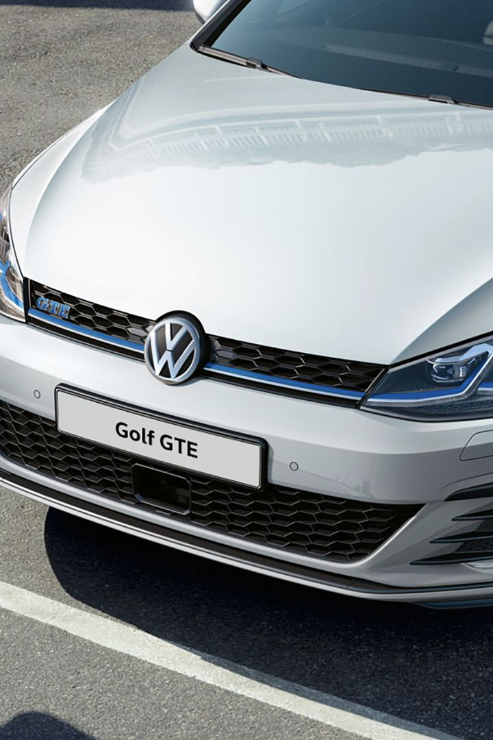 A white Golf GTE parked with a man walking infront