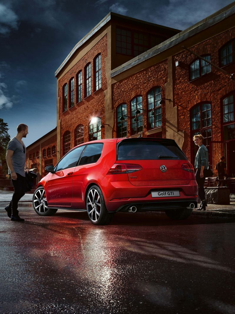 A couple getting in their red Volkswagen Golf GTI