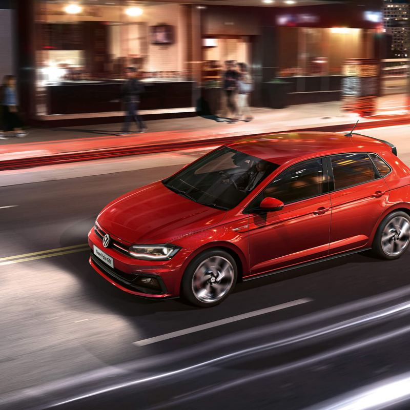 A red Volkswagen Polo GTI driving through a city street in the evening.