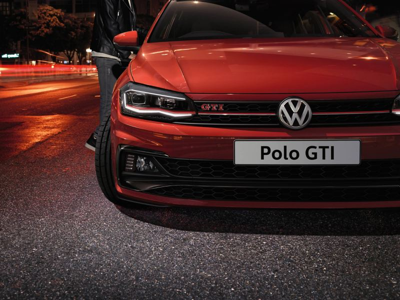 Close up of the front of a red Volkswagen Polo GTI, out of focus lit city street in the background.