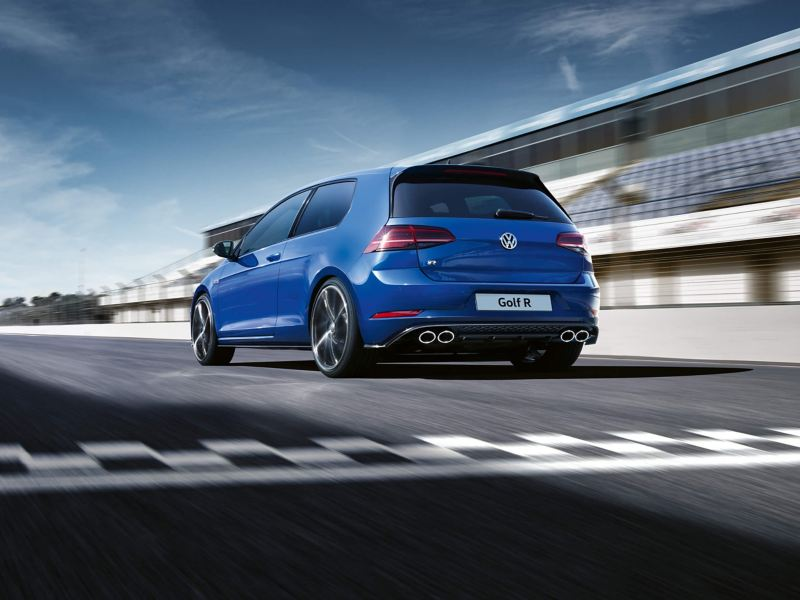 A blue Volkswagen Golf-R driving around a car race track.