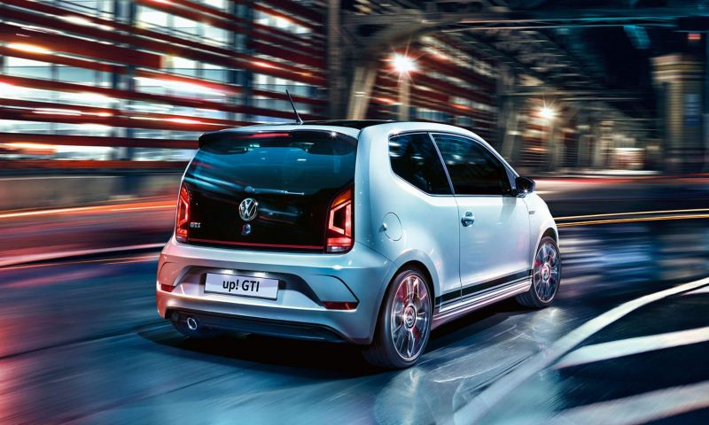 Rear view of a white Volkswagen up! GTI driving through the city street at night.