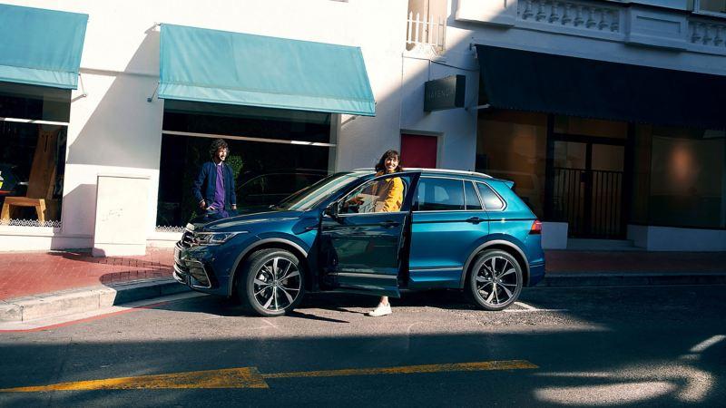 A woman getting in her blue new Volkswagen Tiguan
