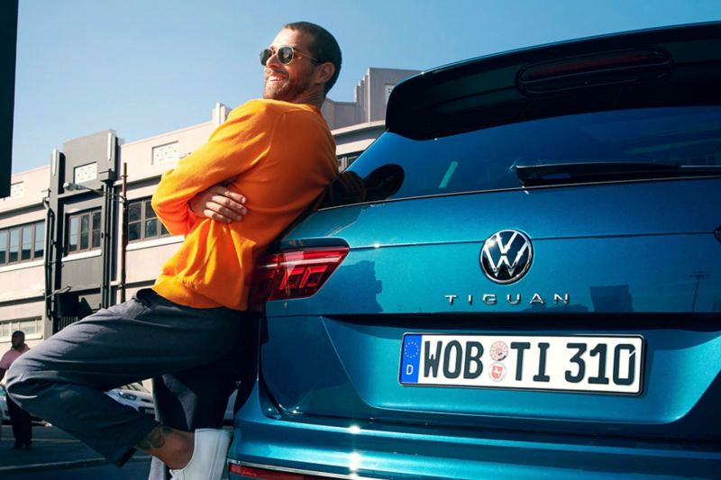 Man with sunglasses leans against rear of VW Tiguan
