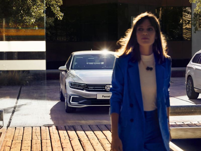 A lady walking away from herSilver Volkswagen Passat GTE.