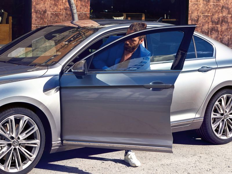 A man getting out of a silver Volkswagen Passat Saloon.