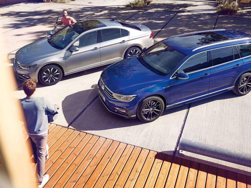 A man is entering a silver Volkswagen Passat Saloon that is parked next to a blue Volkswagen Passat Estate