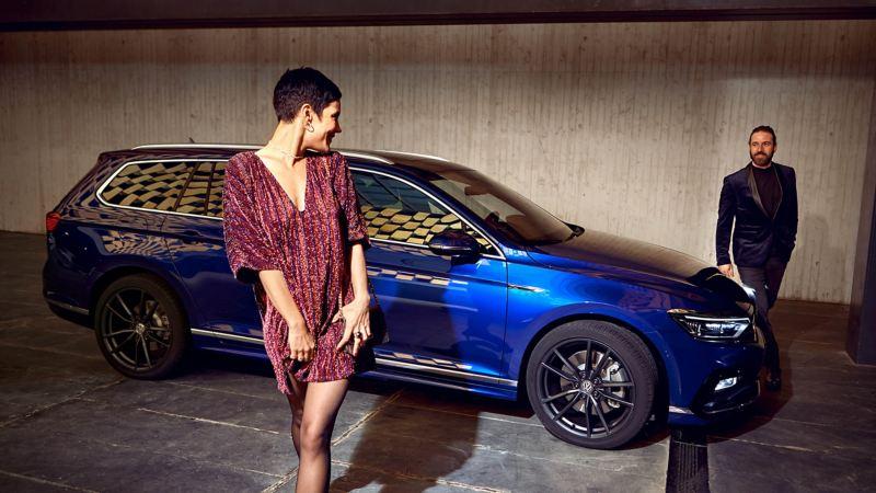 A man and woman in evening dress, next to a blue Volkswagen Passat Estate.