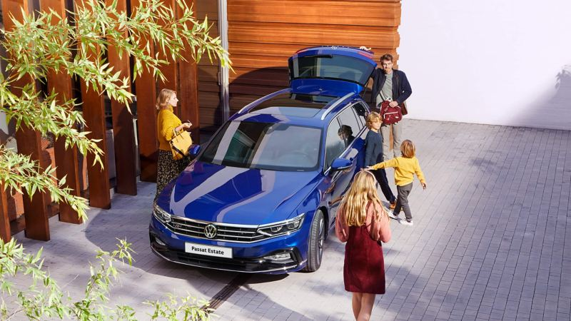 A family outside their home all getting into a blue Volkswagen Passat Estate, going on a trip.