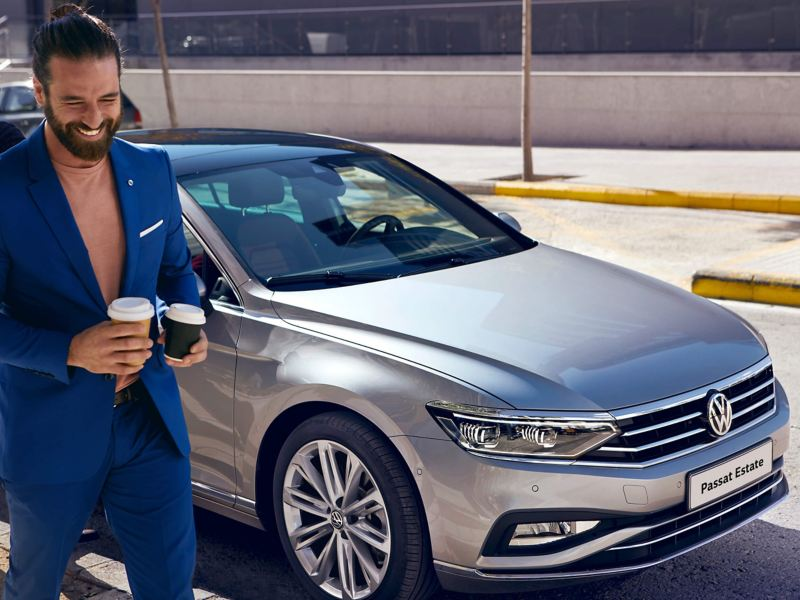 A man holding two coffees, next to a silver Passat Estate.