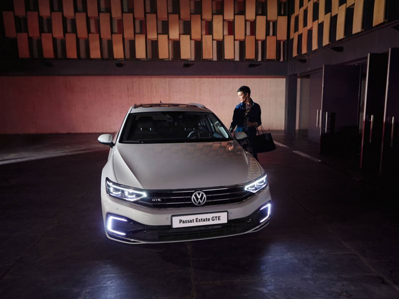 . A white Volkswagen Passat Estate GTE, in a darkened space with a lady getting in.