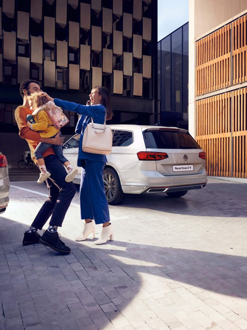 A young family next to Volkswagen Passat GTE and Passat Estate GTE.