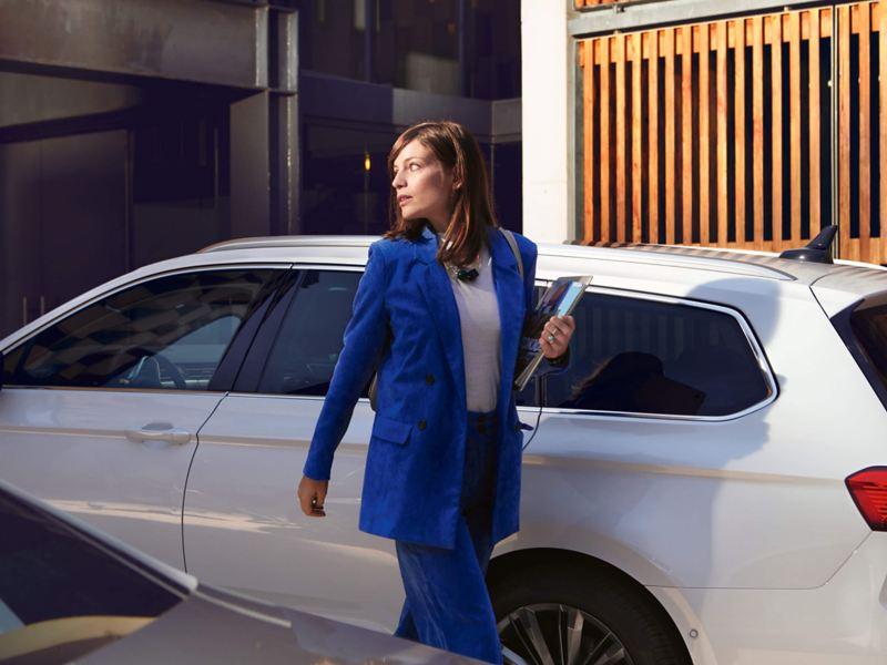 Woman standing near a white Passat Estate GTE