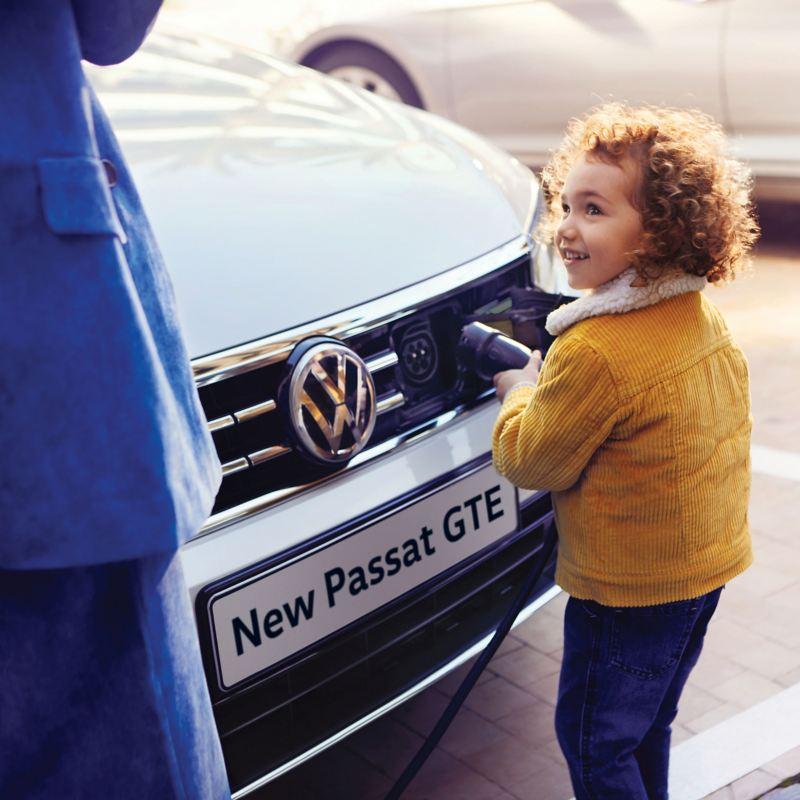 A boy charging a white Volkswagen Passat GTE