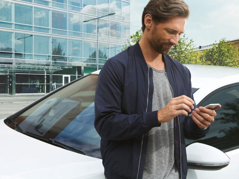A man using his smart phone, next to a sliver Volkswagen e-Golf.